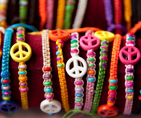 Several colorful, beaded bracelets with larger beads shaped like peace signs