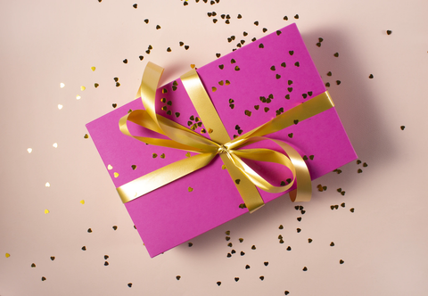 box wrapped in pink paper with gold bow and sprinkled with confetti