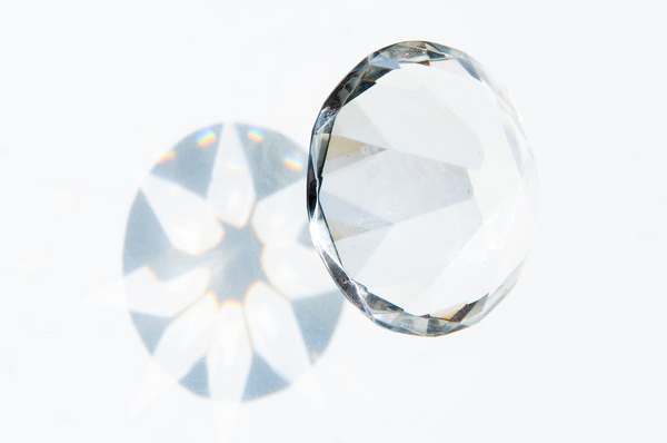a diamond and light refracting from it onto a white background