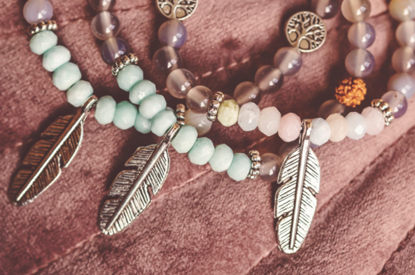 three beaded bracelets, each with a single, silver, feather-shaped metal charm