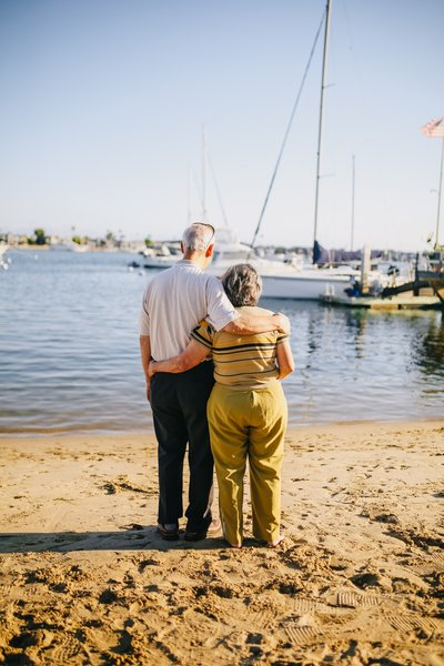 elderly couple embracing by beach