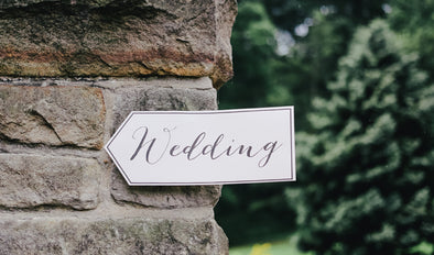 A white arrow sign with wedding written on. Read our blog post on keeping children and toddlers at weddings entertained.