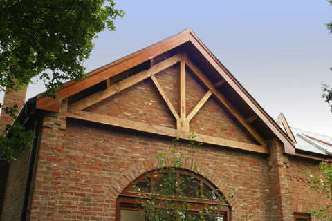 oak king post truss exposed on the outside of the building