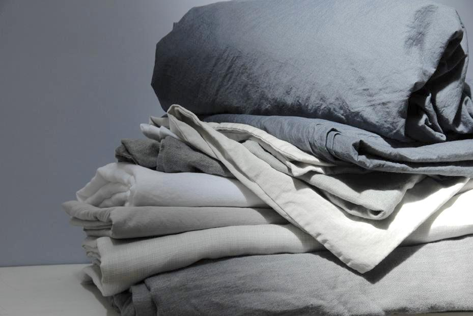 caring for your linens pile of sheets