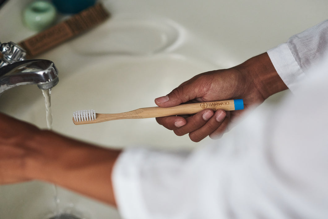 Girl brushing her teeth with a BAMWOO bamboo toothbrush in a villa in Bali, Indonesia