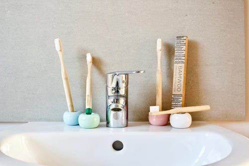 BAMWOO's children's and adult bamboo toothbrushes on the sink in a bathroom