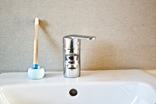Children's bamboo toothbrush in ocean blue from BAMWOO on sink in bathroom