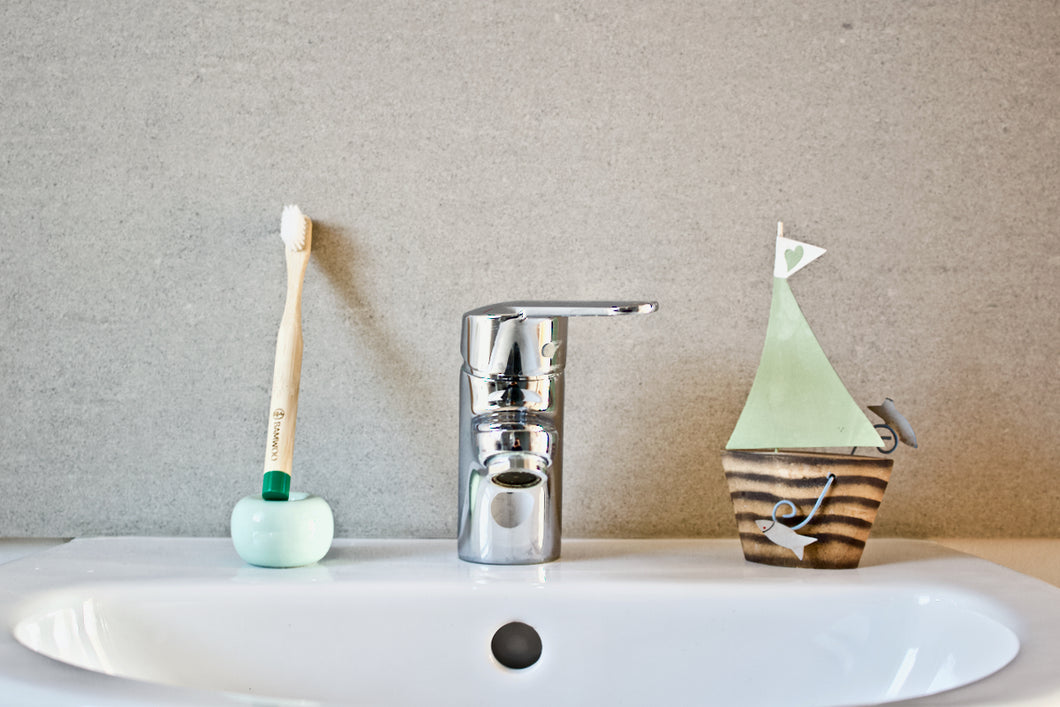 Children's bamboo toothbrush in forest green from BAMWOO on sink in bathroom