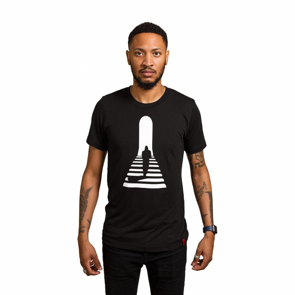 Front of a male wearing a black Line of Vision (LOV) graphic tee