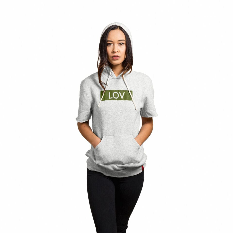 Female wearing an oatmeal colored cut-off hoodie with the Line of Vision brand logo. LOV in blocked border.