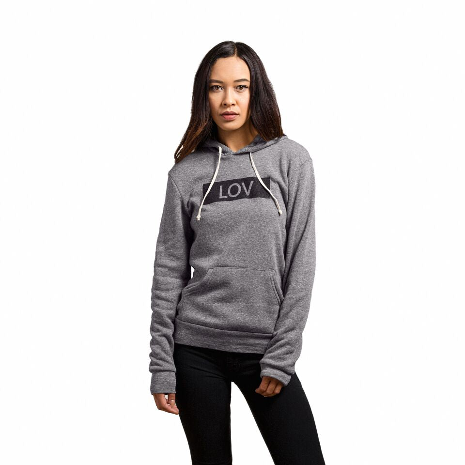 Female wearing a grey hoodie with the Line of Vision brand logo. LOV in blocked border.