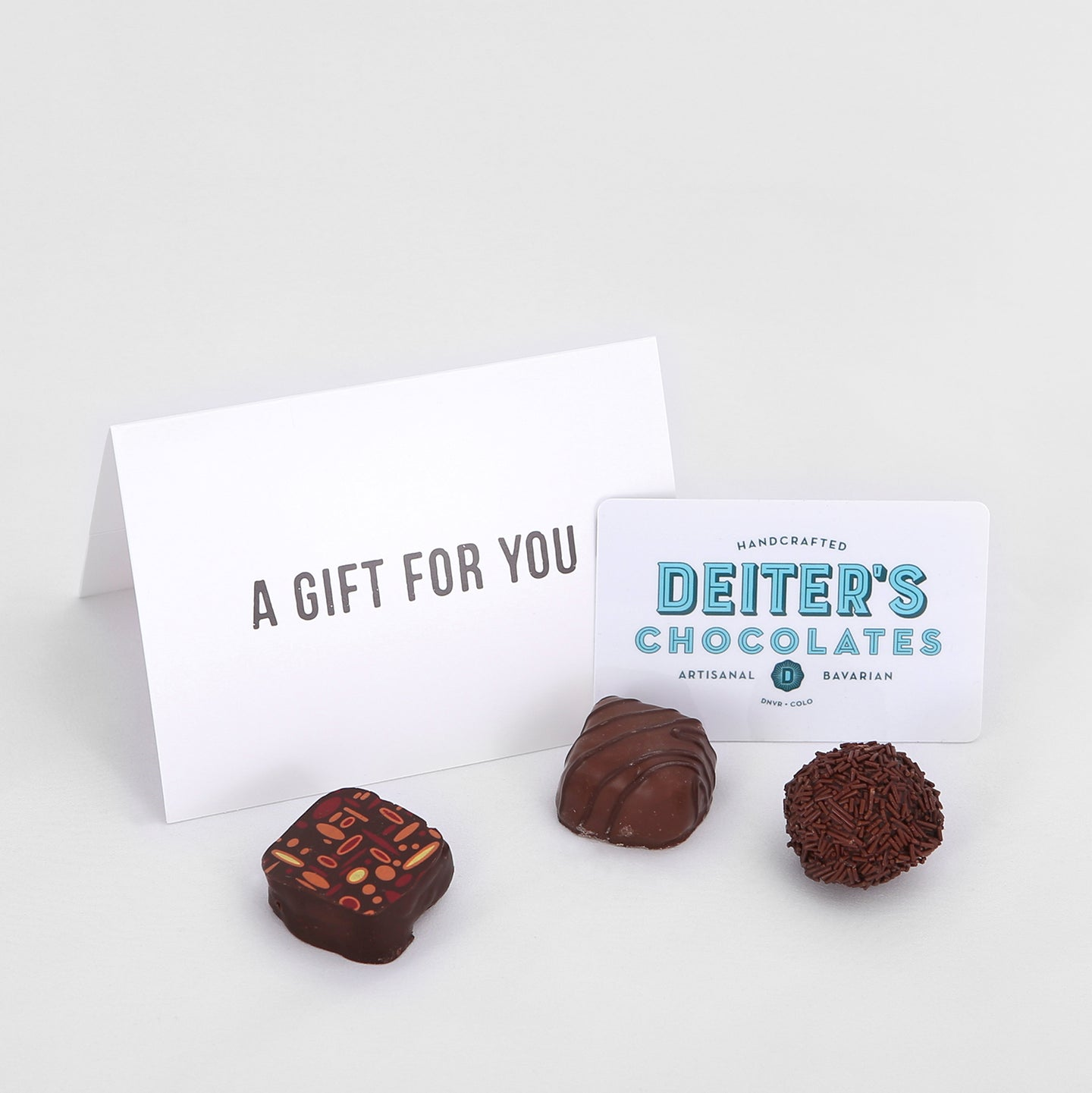 a plastic Deiter's gift card, envelope and three truffles