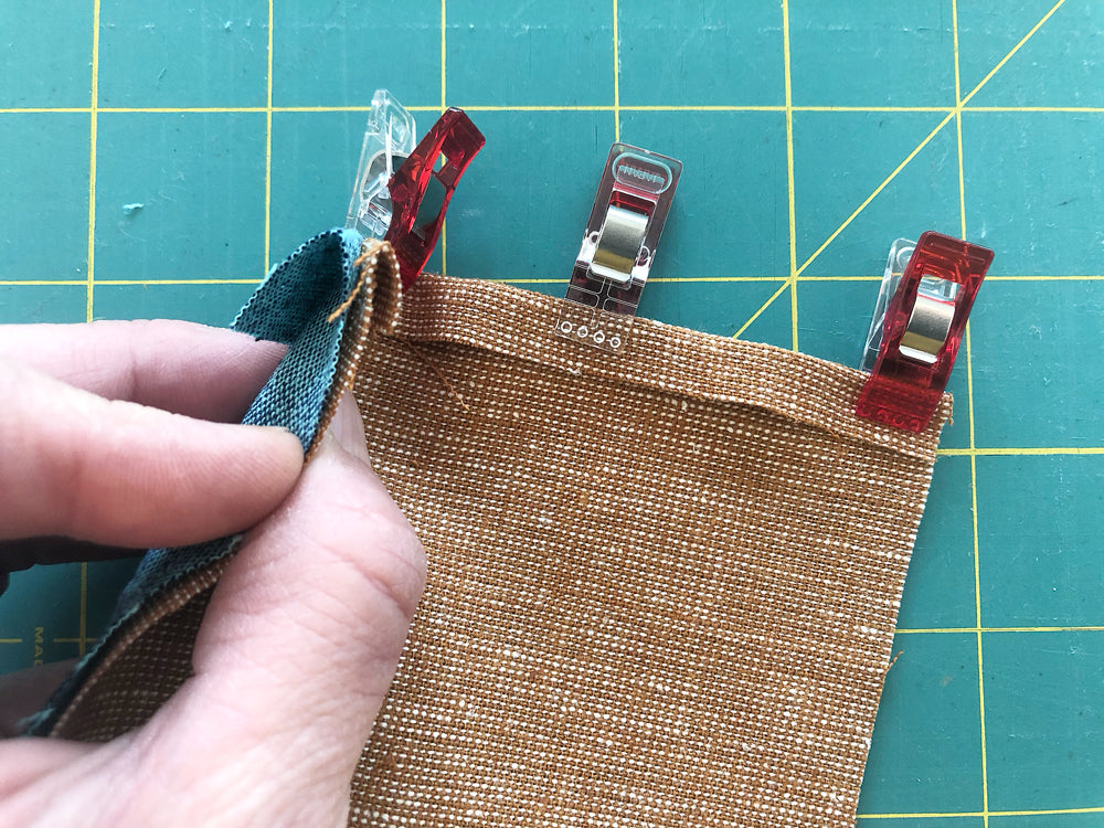 Aligning linen fabrics and securing them with clover clips for hand sewing a flat-felled seam.