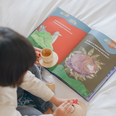 Little girl reading children's book on a bed