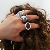 Hand in hair, wearing multiple rings