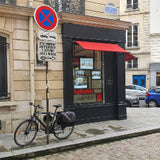 Parisian street view, bicycle against pole outside shop