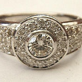 diamond engagement ring with central round stone, diamond halo and band