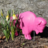PINK BUFFALO LAWN ORNAMENT NEXT TO FLOWERS OUTSIDE