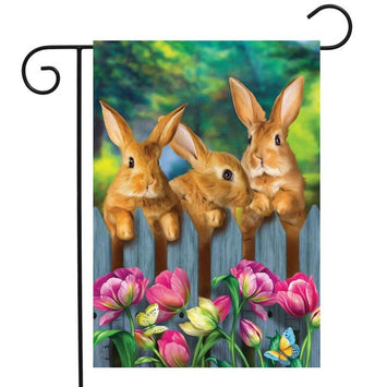 three bunnies behind a fence on a flag with colorful flowers in the front
