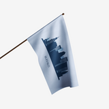 "SKY BLUE FLAG WITH A CITYSCAPE IN THE CENTER AND THE WORD ""BUFFALO"" UNDERNEATH ON A FLAGPOLE"