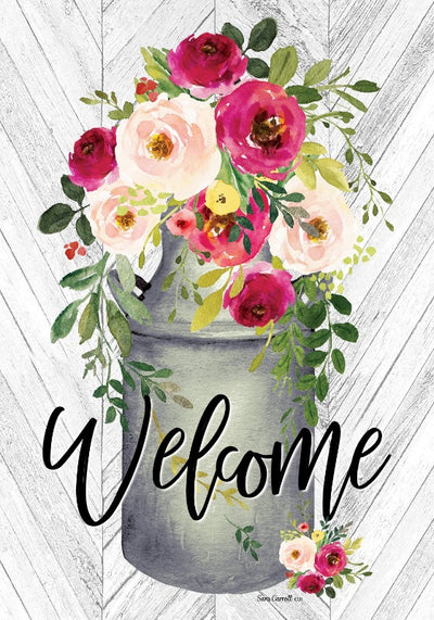 "milk can with flowers and the word ""welcome"" across the bottom"