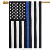 black and white american flag with a single blue stripe down the center on a flagpole