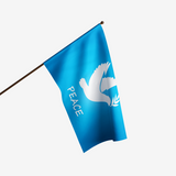"BLUE FLAG WITH WHITE DOVE IN THE CENTER AND THE WORD ""PEACE"" UNDERNEATH IT ON FLAGPOLE"