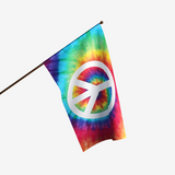 RAINBOW TIE DYE FLAG WITH A WHITE PEACE SIGN IN THE CENTER ON A FLAGPOLE