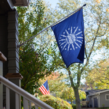 BLUE FLAG WITH A SHORE AND LIGHTHOUSE IN THE CENTER WITH LIGHTNING BOLTS AROUND THE CENTER ON A POLE OUTSIDE