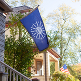 BLUE FLAG WITH A SHORE AND LIGHTHOUSE IN THE CENTER WITH LIGHTNING BOLTS AROUND THE CENTER ON A POLE OFF THE HOUSE
