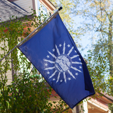 BLUE FLAG WITH A SHORE AND LIGHTHOUSE IN THE CENTER WITH LIGHTNING BOLTS AROUND THE CENTER ON A POLE