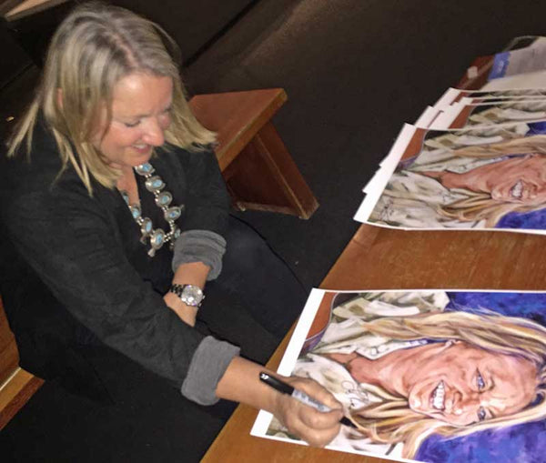 Liz Rose signing fine art print by Robert Hurst