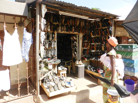 African woman looking at used shoes