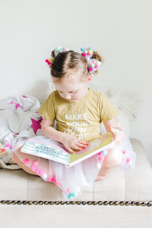 tutu joli pom pom tutu skirt in white for kids with bow hairtie and poms, a child reading Allison in wonderland book