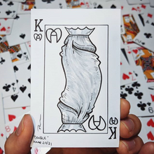 A drawing of a King of hearts playing card but the two heads of the king are actually heads of a penis