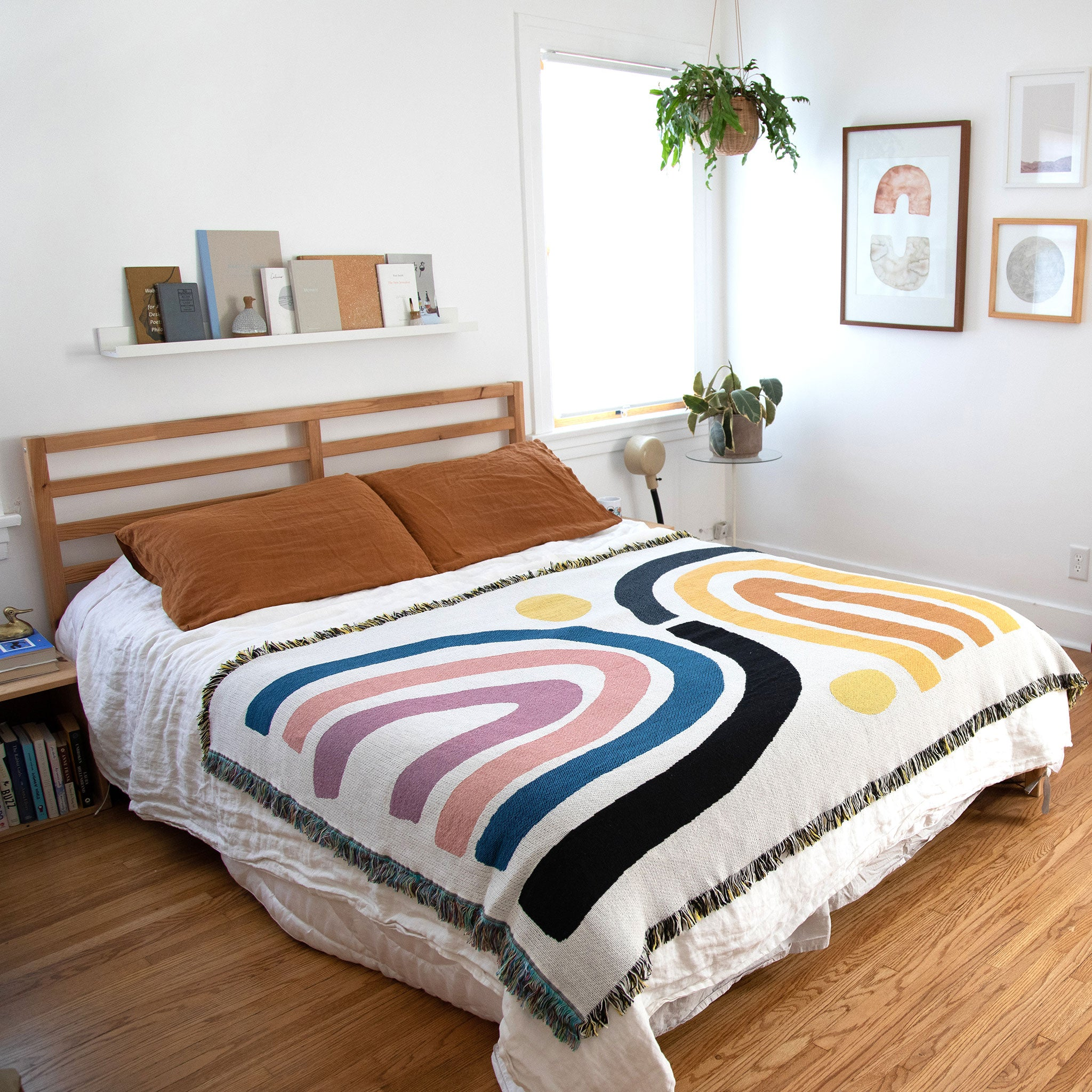 Pastel pink and blue with gold rainbow striped Perry throw by Slowdown Studio on bed in bedroom