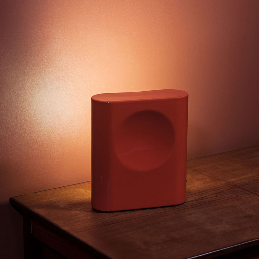 Red ceramic Signal lamp by raawii on bedside table shining light onto the wall