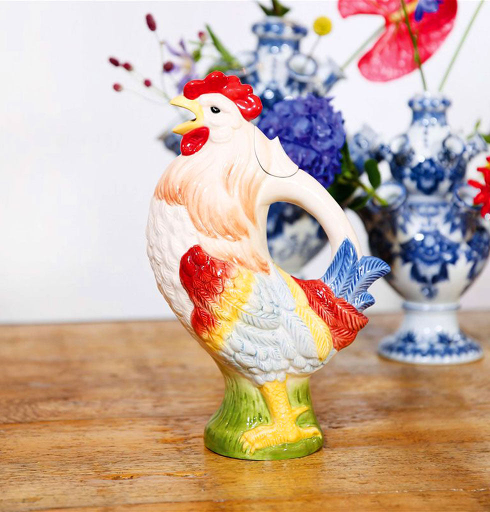 "This ceramic Rooster jug has got us all in a bit of a cock-a-doodle-doo. So much fun for your tableware, imagine the joy, pouring your favourite sparkling water or sangria from this character cockerel jug.  Fill the rooster jug in his back, fit the lid and pour out through his beak  W.A.Green says, ""Don't be chicken, this rooster jug is one clucky bird""."