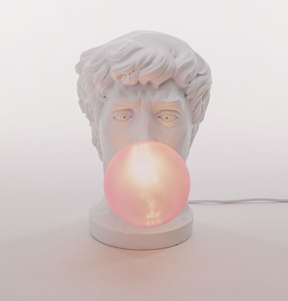 "Wonder Lamp.  Do you ever wonder what the statues in museums get up to when we're not looking. This is Michelangelo's David reimagined by new Seletti designer Uto Balmoral. ""David is really bored, there are no visitors in the museum so to pass the time he's having fun blowing a giant bubble with bright pink gum"".  Occasional lamp featuring the white head of a man blowing a pink bubble. £239 wagreen.co.uk"
