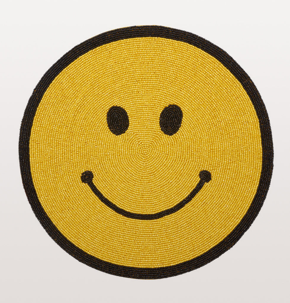 Smile and BEad happy! We've always been a fan of the iconic acid house smiley face for it's funky positive vibes and these hand beaded happy yellow smiley face placemats are just the thing to perk up your table and your life.   Hand made in India with glass beads these smiley face table mats have a smooth wipeable backing.