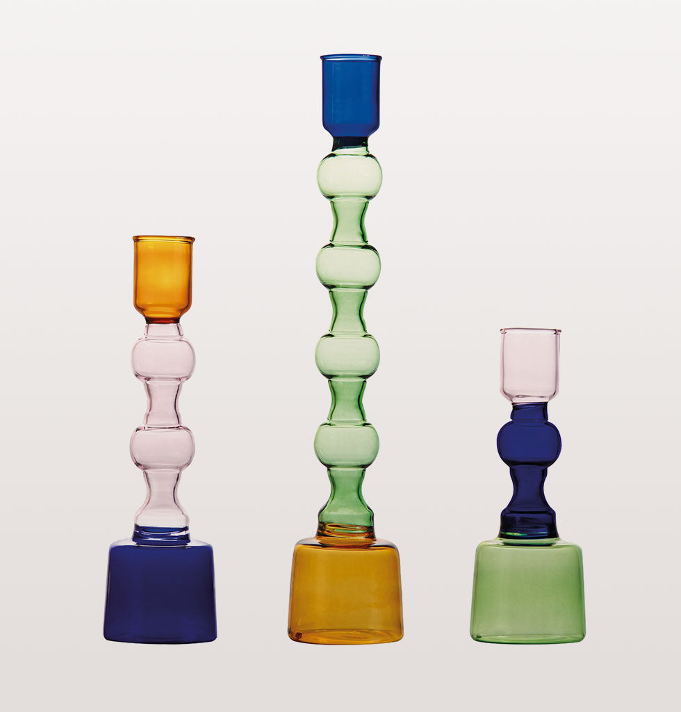 "Elegant set of 3 glass candle holders in fun pops of colour.  Perfect to add a touch of brightness in darker nights.  Glass coloured candle stick holders for the dinner table or mantlepiece.  The colour combinations of blue, green, amber and pink glass work in easy harmony to give your home an elegant uplift.  W.A.Green says, ""The coloured glass gives these candle stick holders a real elegance and soft quality"".   Set of 3 glass, multicoloured candle stick holders."