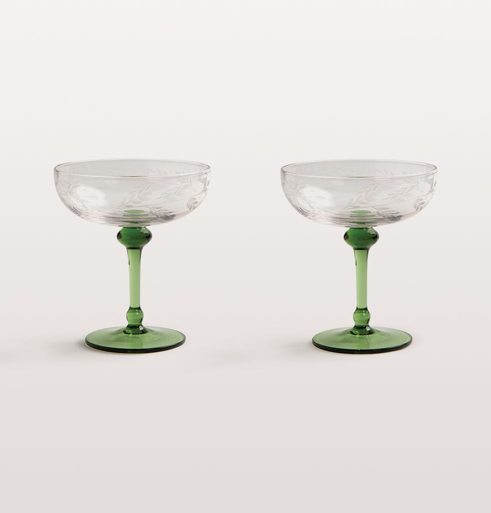 It's always the right time of day for Champagne. These beautiful Champagne coupe glasses with their long green stems make every sip memorable.  The subtle leaf detail on the clear glass bowl is an unexpected touch which paired with the green glass stem makes this Champagne coupe glass set something to be cherished.  Set of two Champagne couple glasses, presented in gift box.