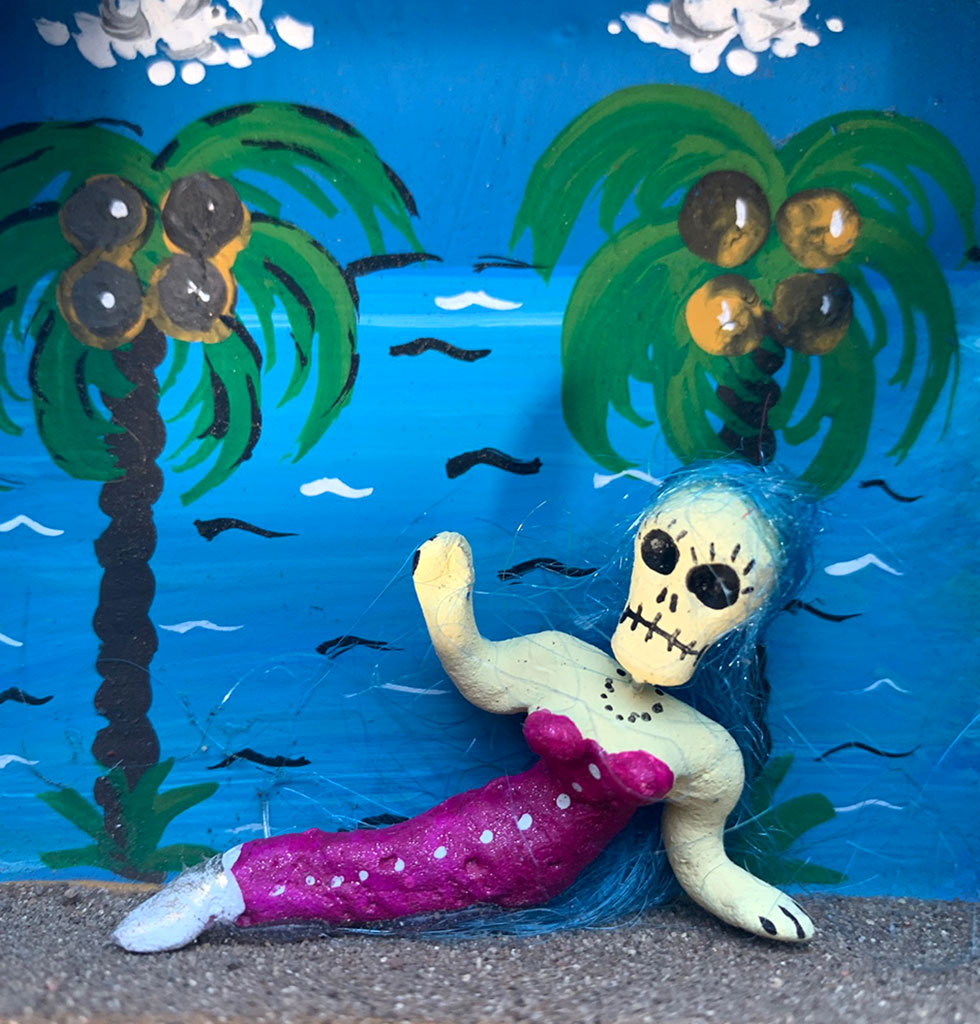 MILAGROS | Unique Mexican hand crafted decorative tin nicho box depicting a gloriously seductive Day of the Dead skeleton mermaid.   Mexican traditional tin crafted shadow box wall decoration. Nicho box in blue featuring a tropical beach design with coconut trees and white fluffy clouds. £58 wagreen.co.uk