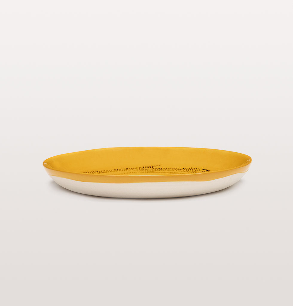 Ottolenghi x Serax. Sunny Yellow and Swirl Dots Black extra small plate side view. £16 wagreen.co.uk