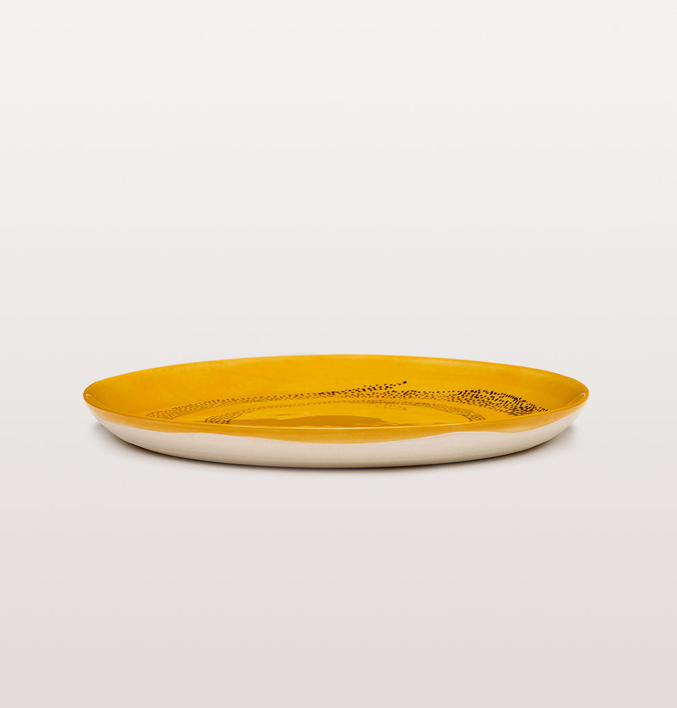 Ottolenghi x Serax. Sunny Yellow and Swirl Dots Black medium plate side view. £25 wagreen.co.uk