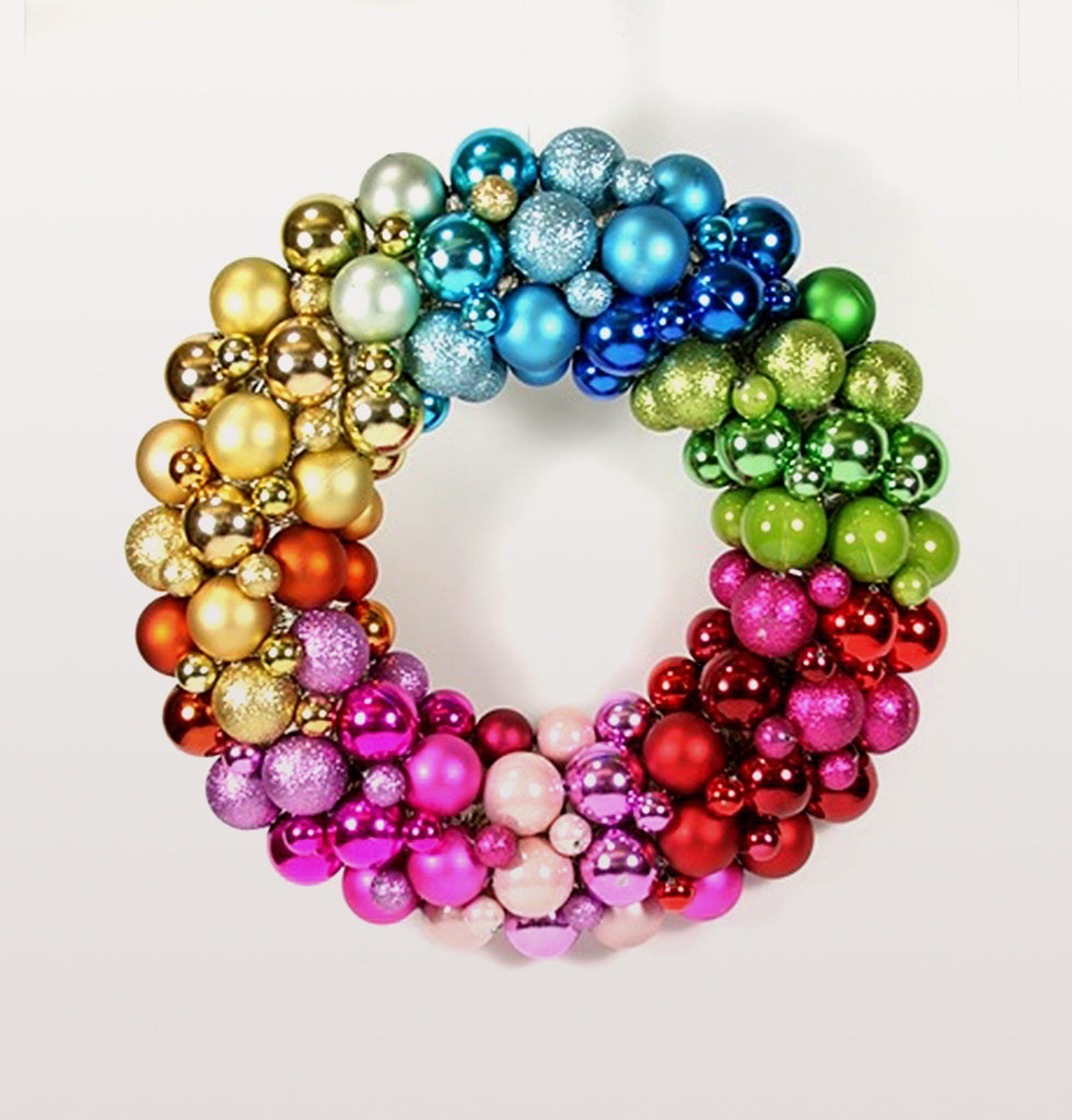 Rainbow ball encrusted baubel decorated Christmas door wreath. Multi coloured different size baubles form an ombre rainbow round door decoration