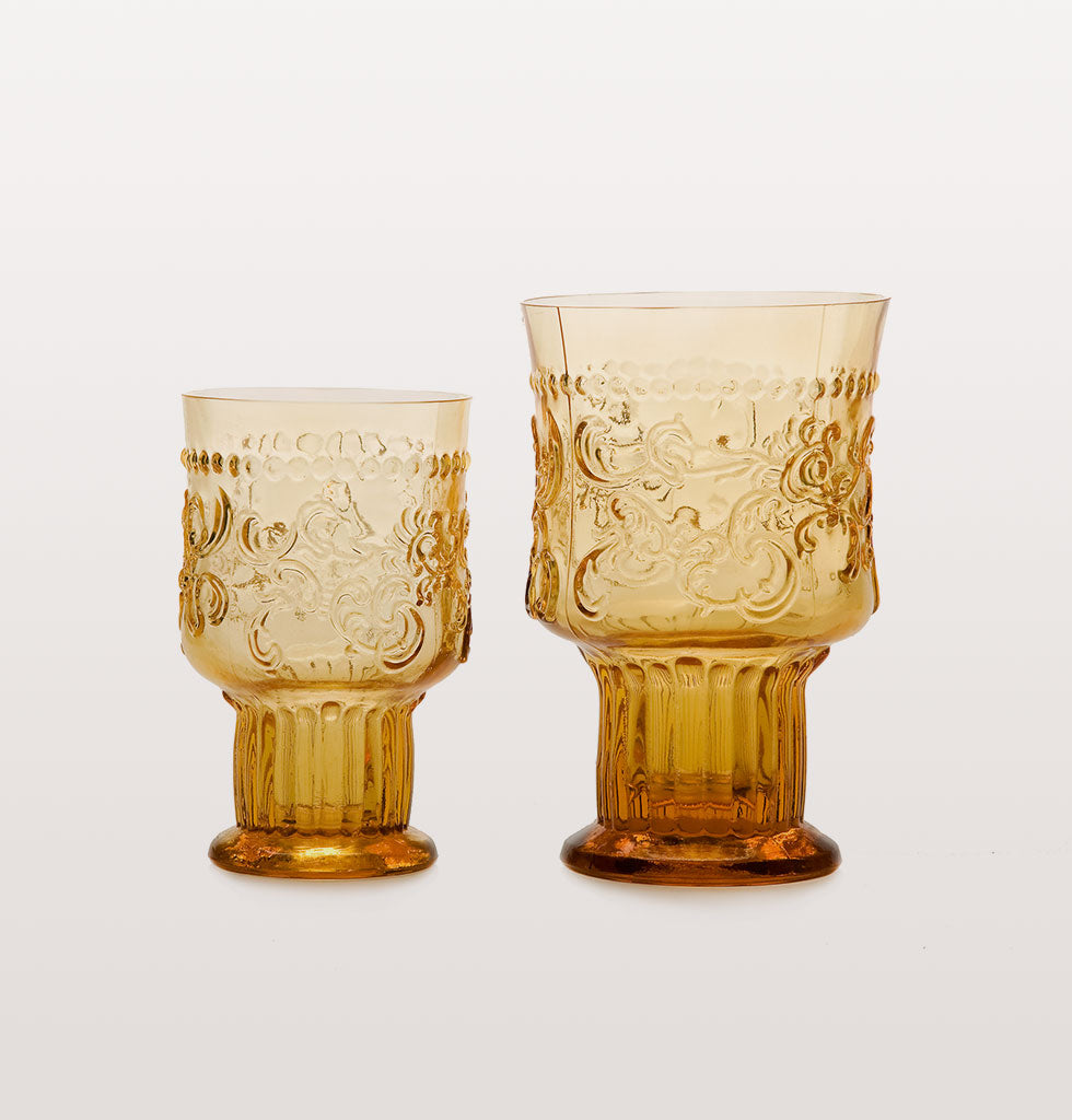 Traditional Portuguese fleur de lys goblet shaped drinking glasses. Perfect summer wine glass for outdoor dining or indoors. Portuguese fleur de lys pattern artisan glassware. Coloured glass and stunning design for unique coloured tablescape. Set of two goblets available in either pink, amber and champagne.