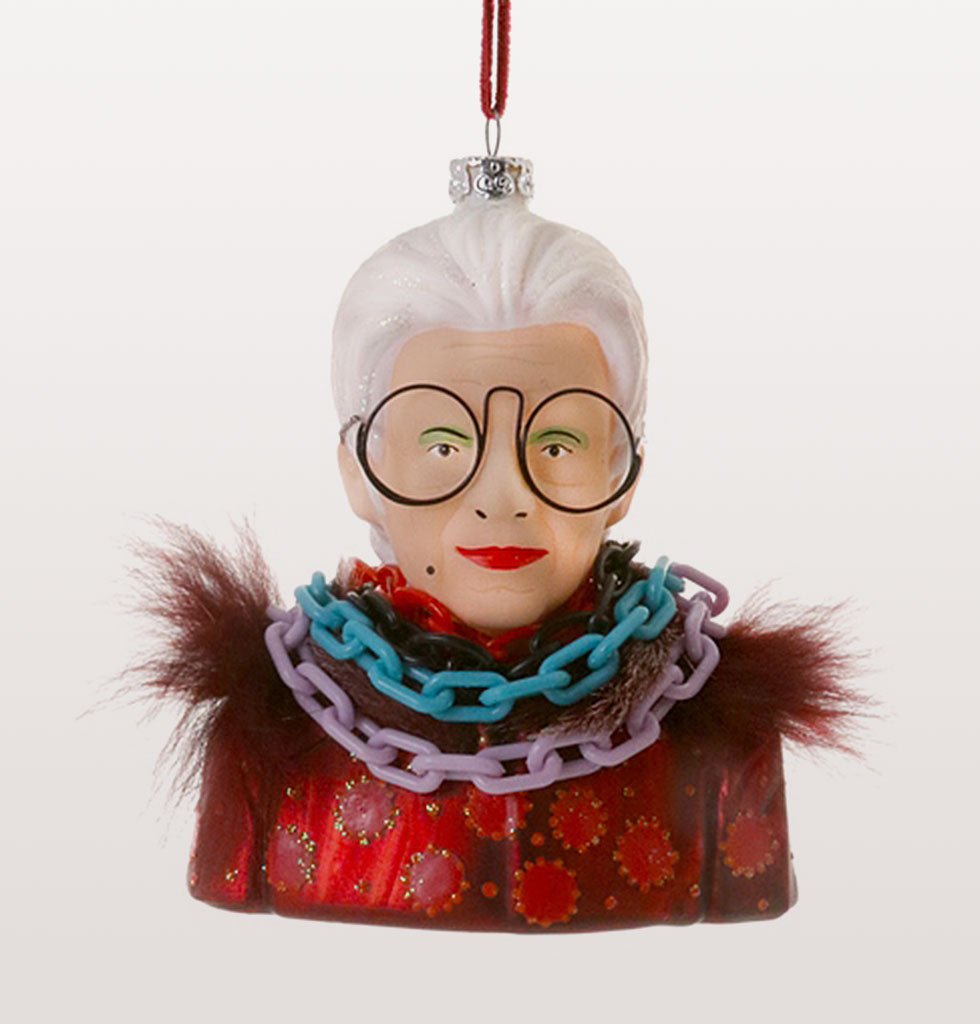 New York fashion legend Iris Apfel has to be number one on our list of fantasy Christmas dinner guests. Here wearing her trade mark glasses and piles of jewellery she's here to make sure your eclectic Christmas tree is as fascinating as her.  Glass ornament with faux fur, glitter and plastic jewellery details.