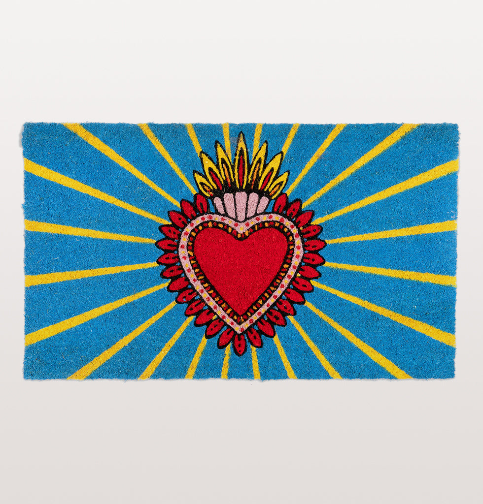 BIENVENIDO! Home is where the heart is and nothing says welcome home more than this bright blue and yellow doormat. It's bold and striking design features a traditional Mexican milagros, a protective charm in the shape of a decorated heart.