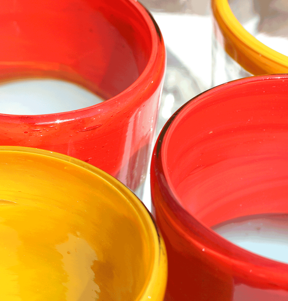 Close up of mexican glass coloured yellow and orange tumblers
